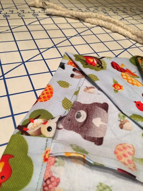 Opening in slip case for cord in baby clothes hamper bag